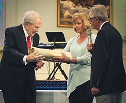"The Larson family presents the Torah to Dr. M.G. ""Pat"" Robertson. Photo courtesy of Elisa Sosa."