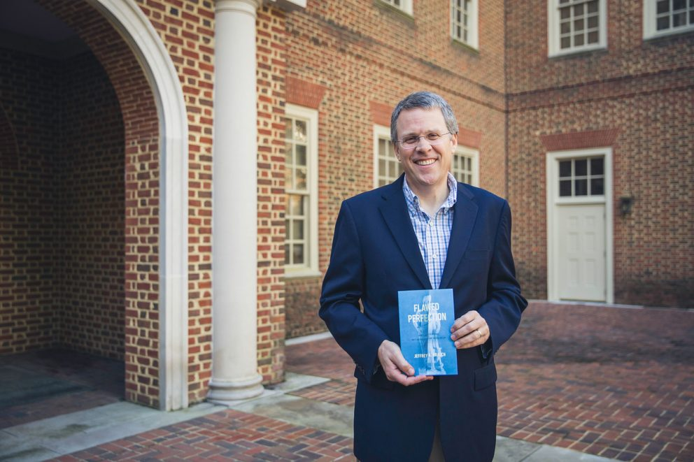 Regent University's law school professor Jeffrey Brauch holds his recent book 'Flawed Perfection: What It Means To Be Human & Why It Matters For Culture, Politics, And Law.'