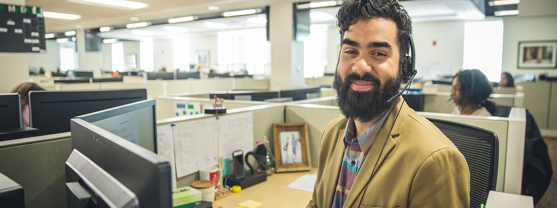 A Regent University employee at his desk.