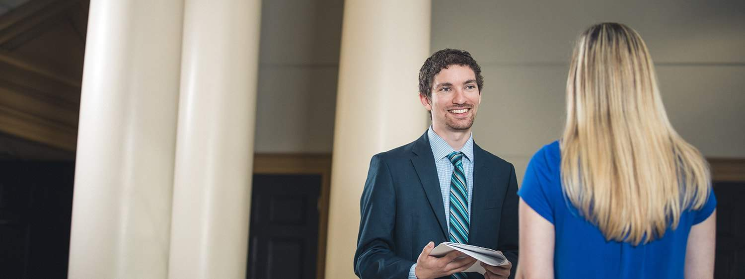 One graduates smiles at another: Explore the online MA in Law - Healthcare Law program offered by Regent University.