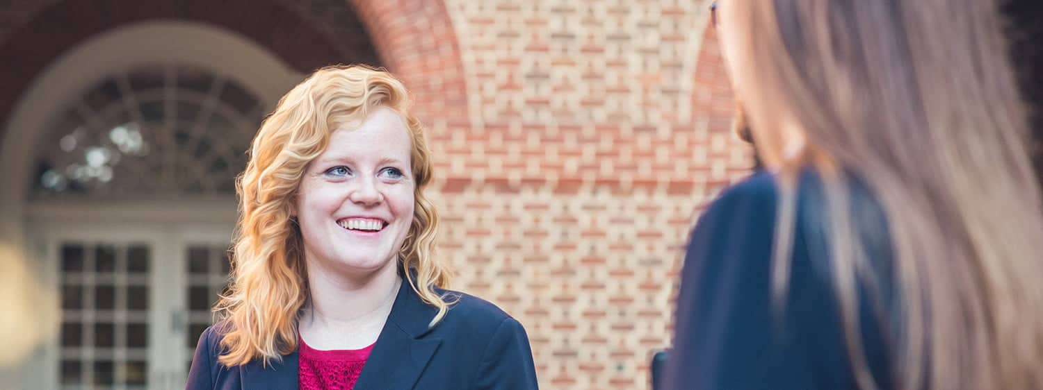 One graduate smiles at another: Pursue the MA in Law – Nonprofit Organization Law degree at Regent University.