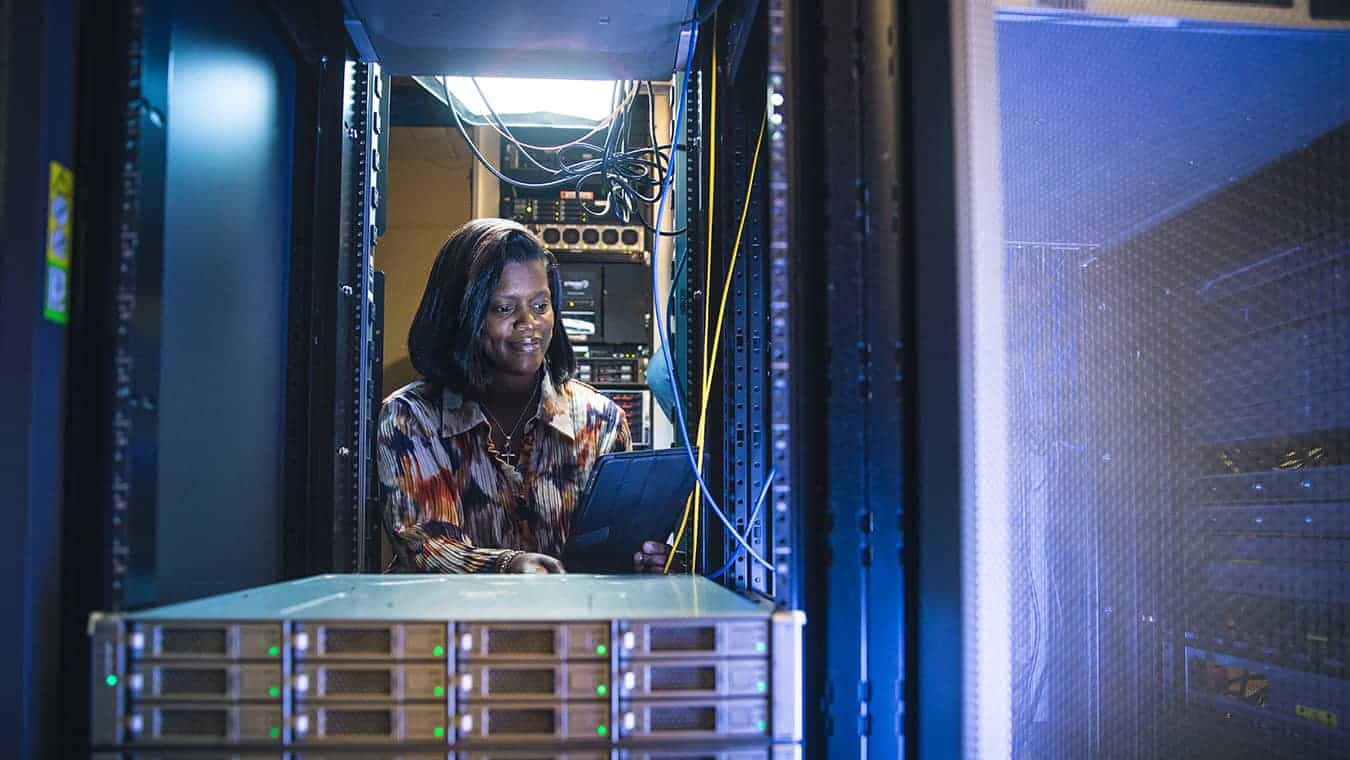 A lady in a server room: Pursue a Certificate of Graduate Studies in Cybersecurity Policy at Regent University.
