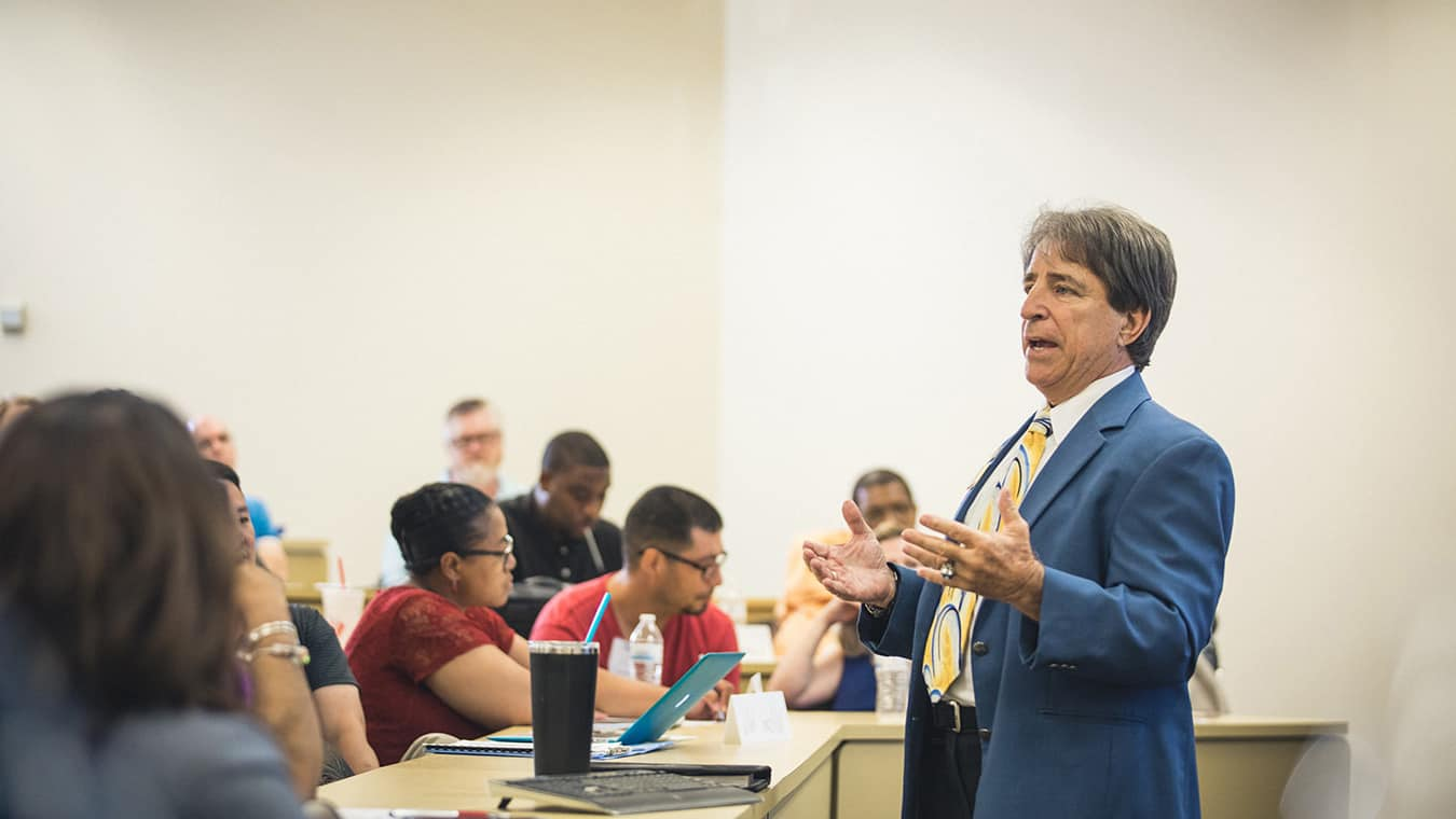 A professor teaching a class: Be equipped to excel through Regent's Ph.D. in Education.