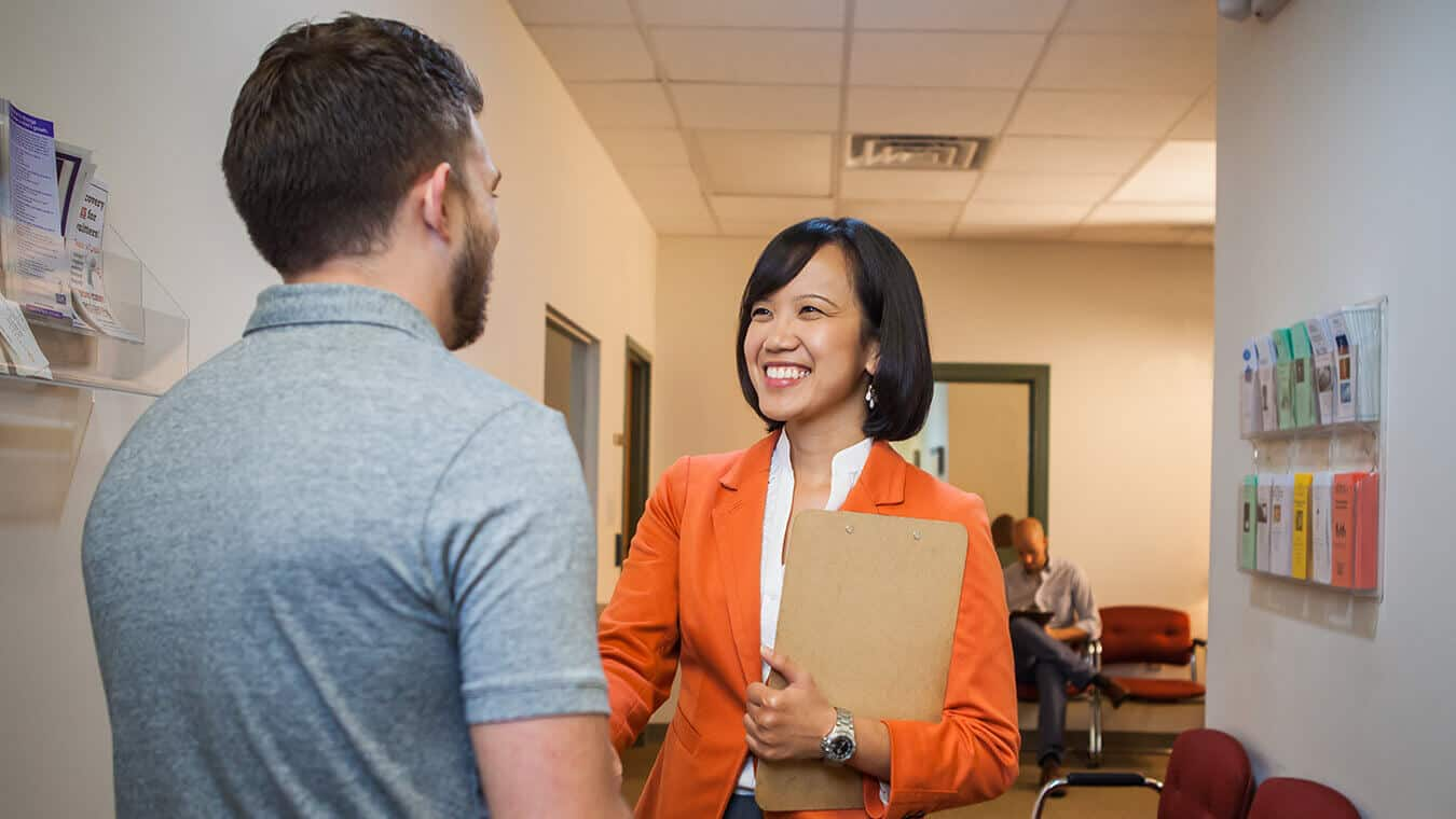 A professor greets a visitor at Regent, a university that offers a clinical mental health counseling program.
