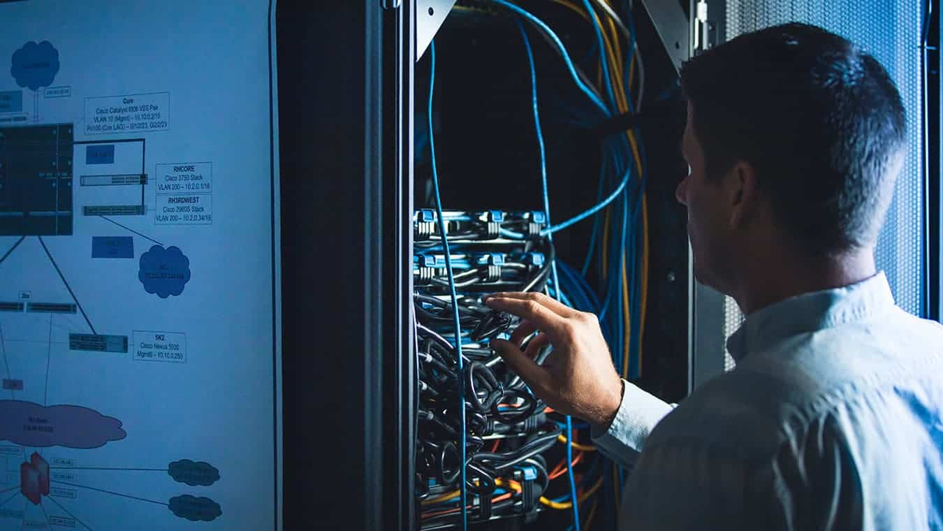 A person works in the server room: Explore Regent's MA in National Security Studies - Cybersecurity Policy program (online / Virginia).
