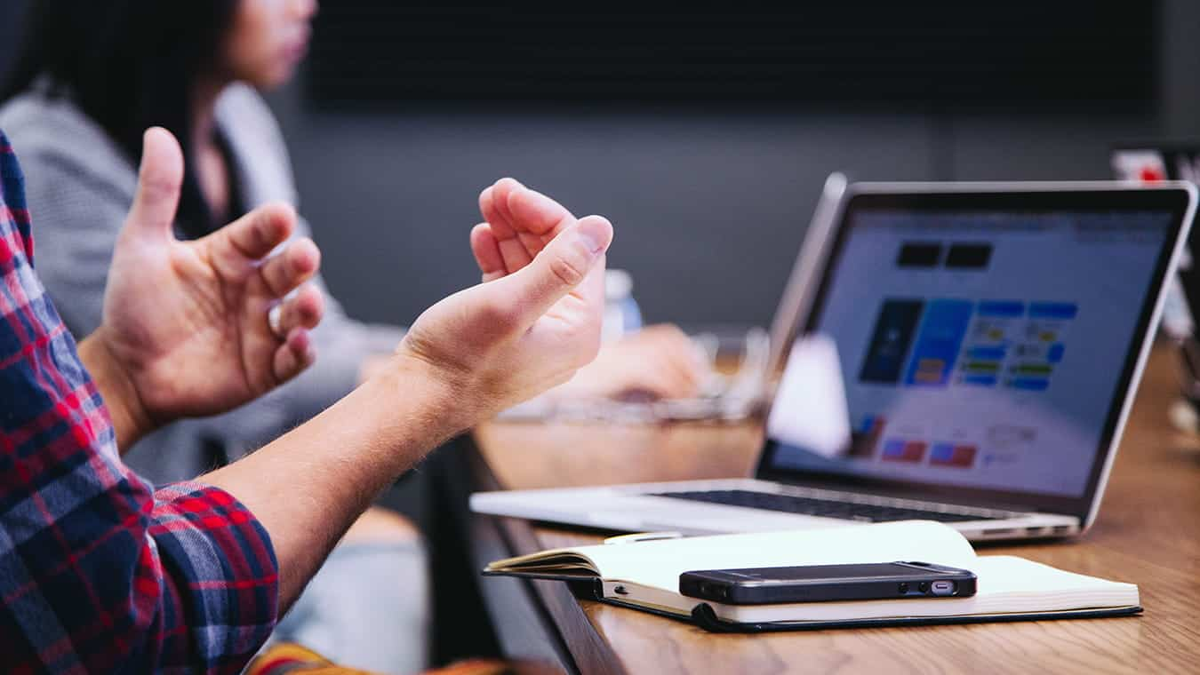 Hands during a meeting: Explore Regent's MAOL degree program with a concentration in Small Business Technology Management.