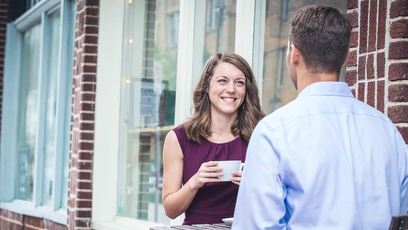 A lady smiles during a conversation: Explore Regent's online master's in psychology – leadership coaching program.