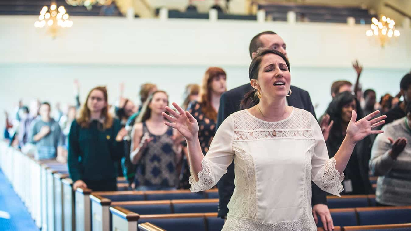 People worshipping during a chapel service: Explore the PhD in Renewal Theology - Church History program at Regent University.