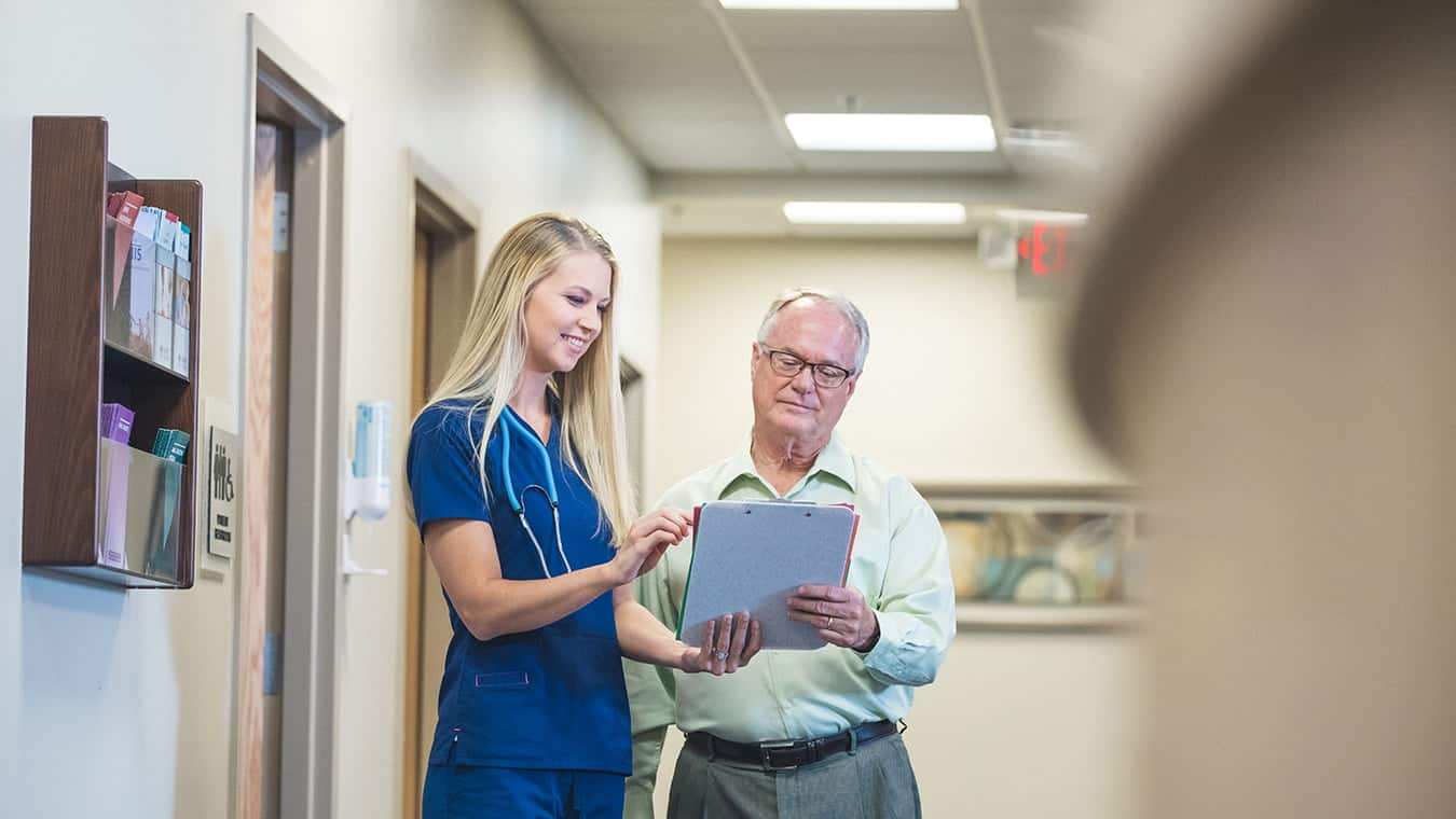 A nurse shows a document to a patient: Explore the MA in Government - Healthcare Policy degree program offered by Regent University.