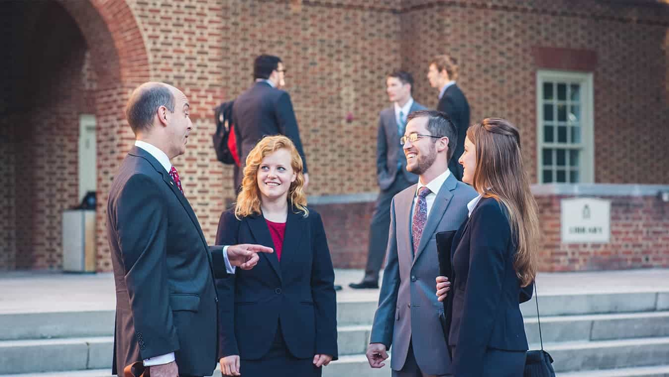 A professor interacts with students: Explore the MA in Government - International Relations degree program offered by Regent University.