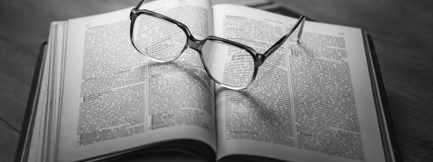 Glasses resting on an open book: Regent University offers a Christian theology certificate program online and in Virginia Beach.