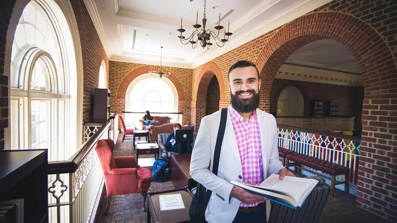 A graduate at the library: Pursue your Master of Arts in Journalism degree online at Regent University, Virginia Beach.