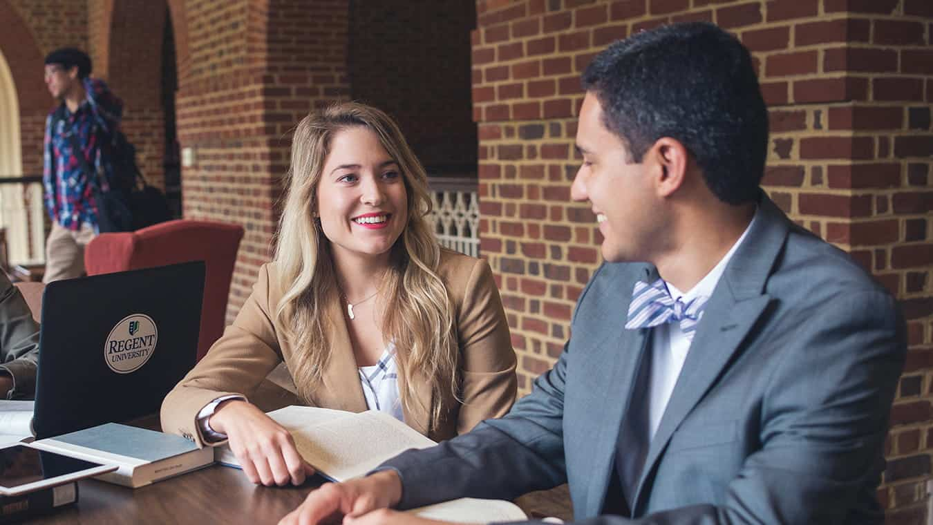 Two graduates at the library: Pursue your Christian leadership and management degree online at Regent University