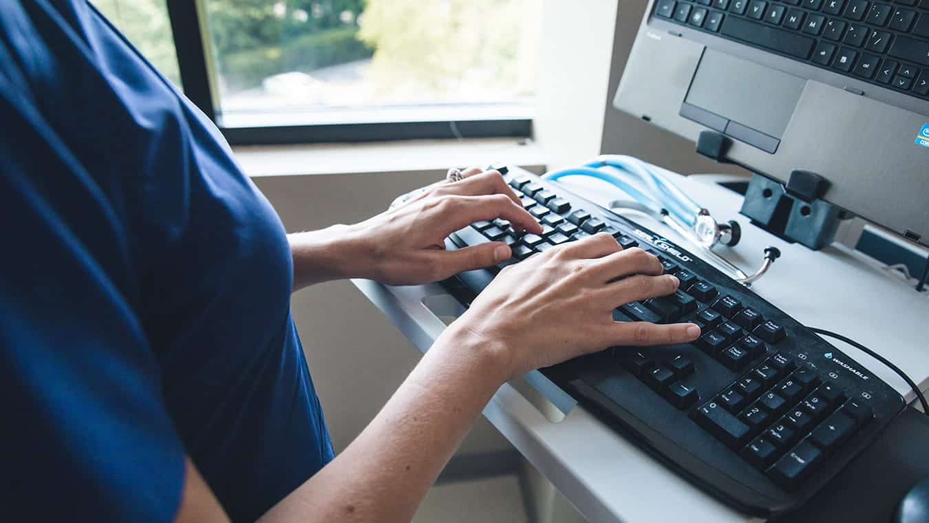 A healthcare professional typing: Explore Regent's online MS in Health Information Systems Administration degree program.
