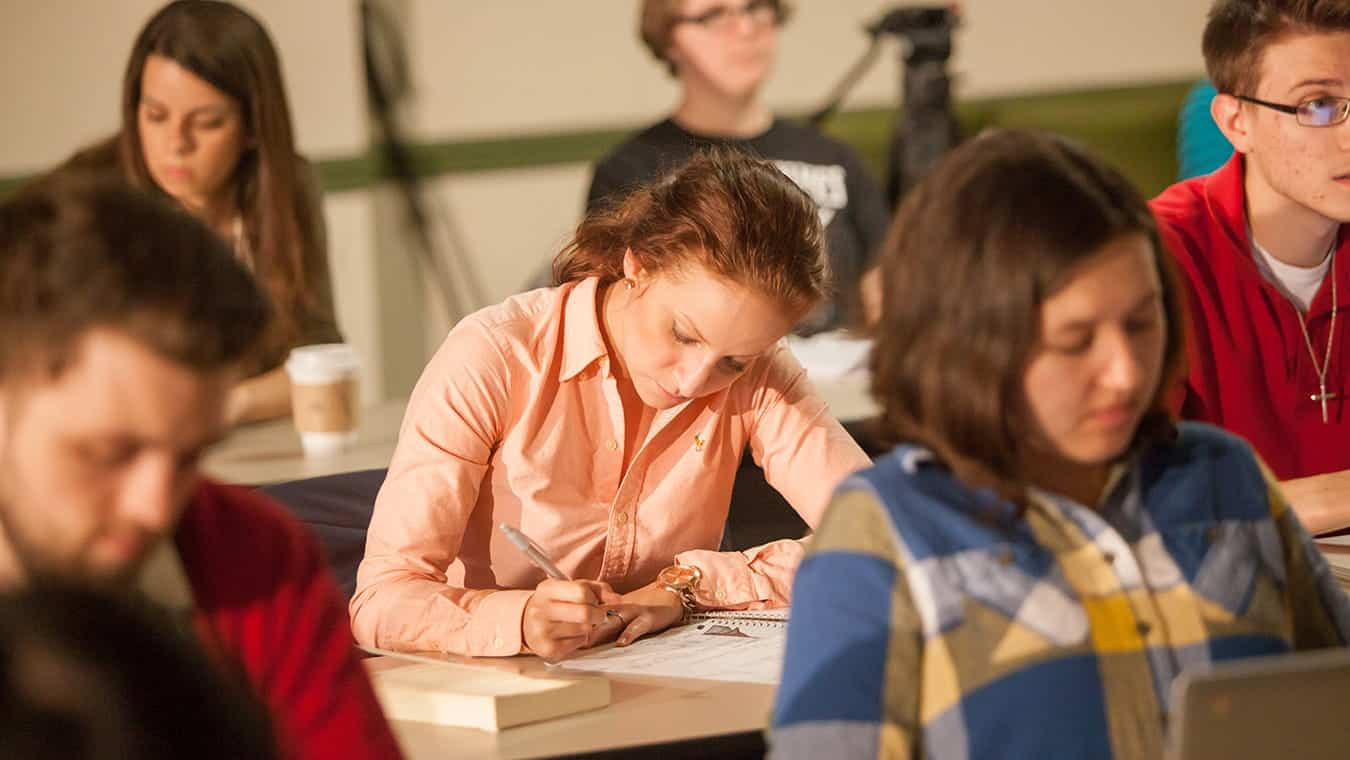 Students writing during class: Pursue an Associate in Business degree at Regent University.