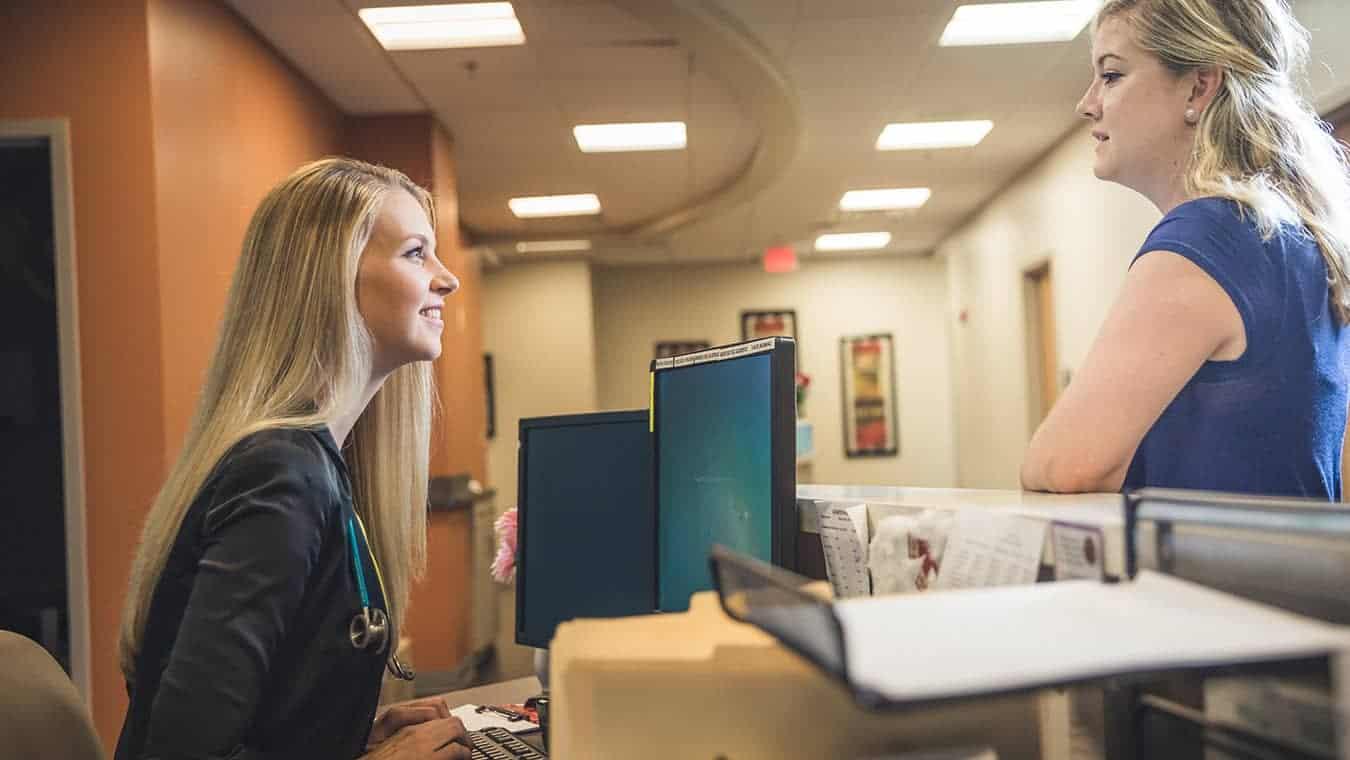 A healthcare professional talks to a guest: Pursue Regent's Nursing Home Administration program online or in Virginia Beach, VA 23464.
