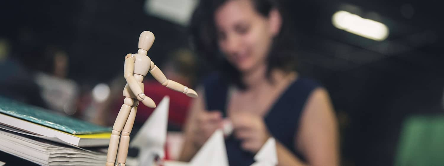A figurine, with a student in the background: Regent University offers a minor in art on campus in Virginia Beach, VA 23464.
