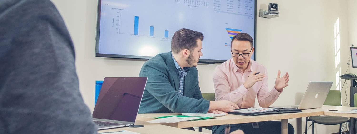 Professionals at a meeting: Pursue your master's in business analytics (MSBA) degree at Regent University.