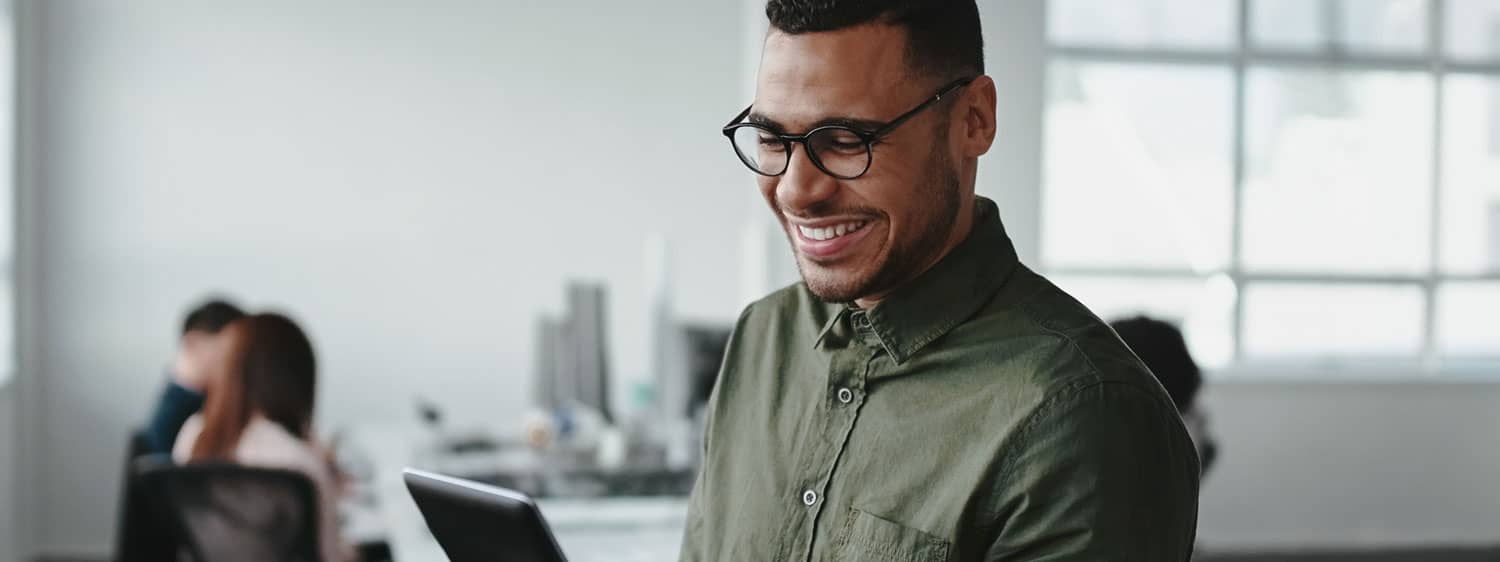 A person smiles while looking at his laptop: Pursue a Ph.D. in Education – Educational Technology and Online Learning degree at Regent University.