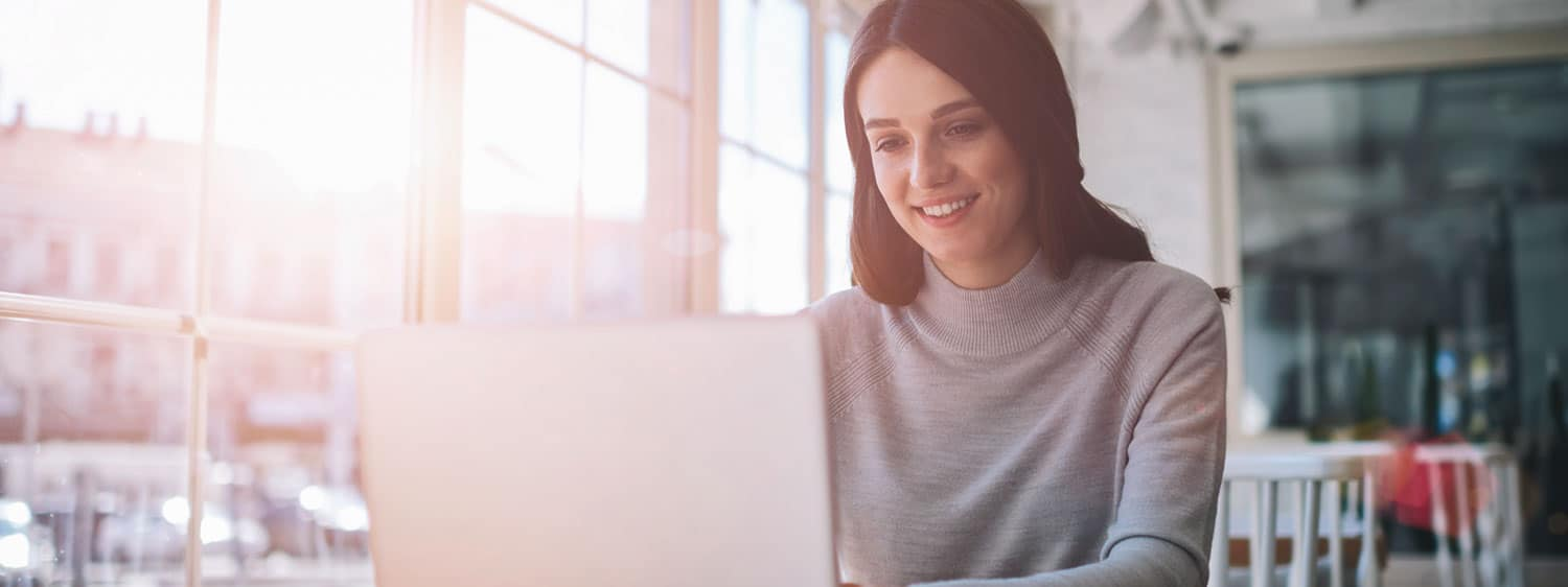 A lady looking at her laptop: Explore the Bachelor of Science in Professional Studies - Communication Studies program offered by Regent University.