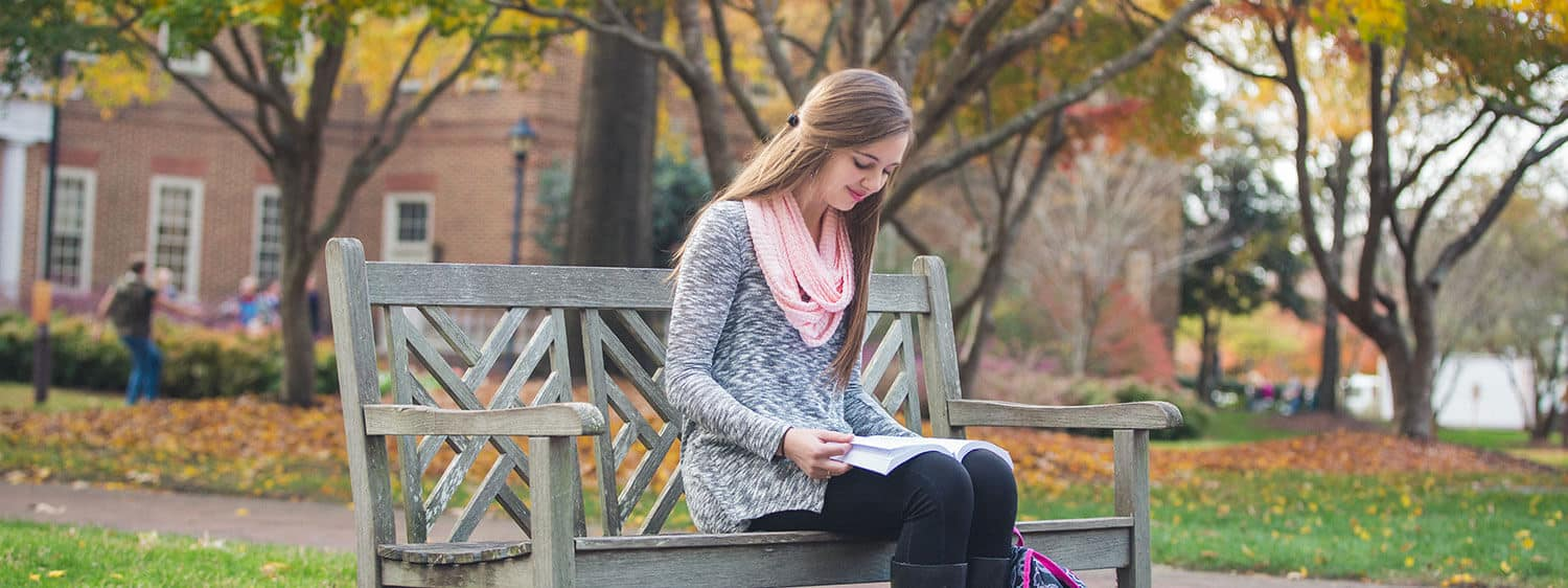 A student reads on Regent University's campus in Virginia Beach.