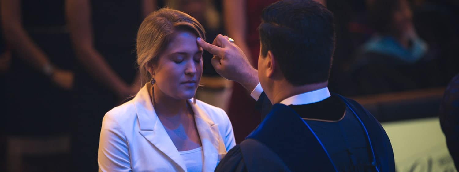 A student of Regent University's Divinity school being anointed during the commissioning service.