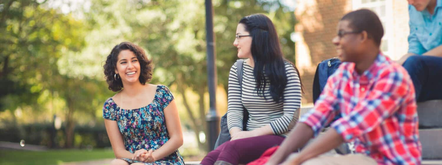 Students chat at Regent University, which offers a community college transfer guide.