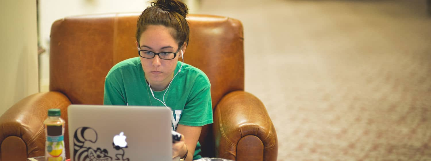 A student works on her laptop at Regent University's library in Virginia Beach.