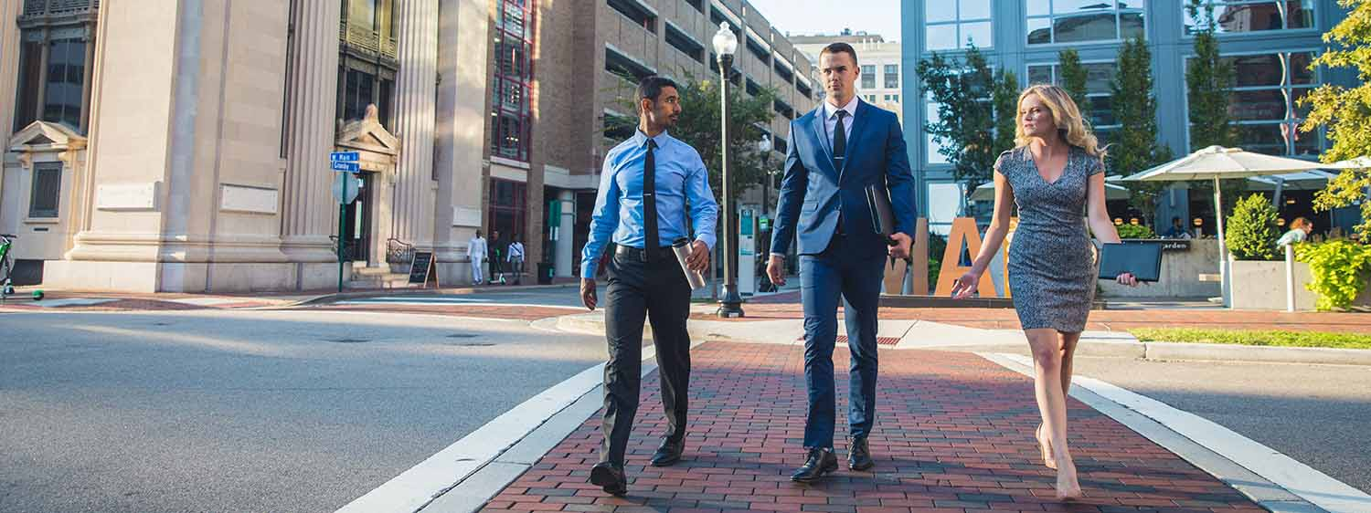 A group in professional attire crosses a road in Norfolk, Virginia.