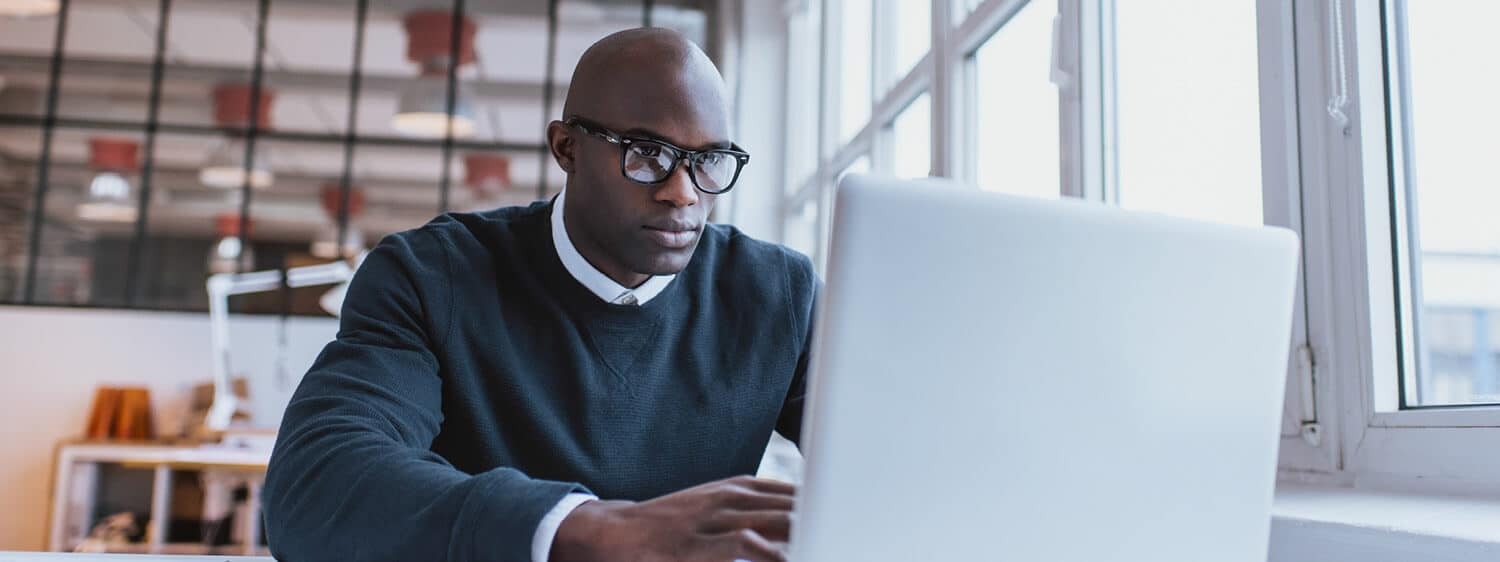 A professional looks at his laptop: Pursue your product management MBA online at Regent University.
