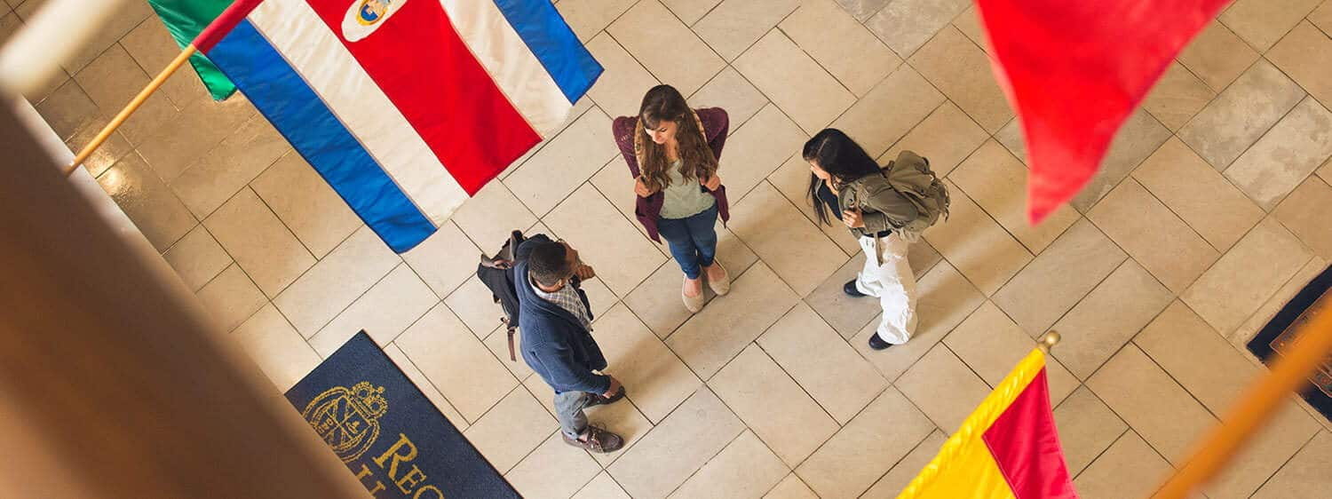 Students at the foyer of Regent University's library, which bears flags of our international students' countries.