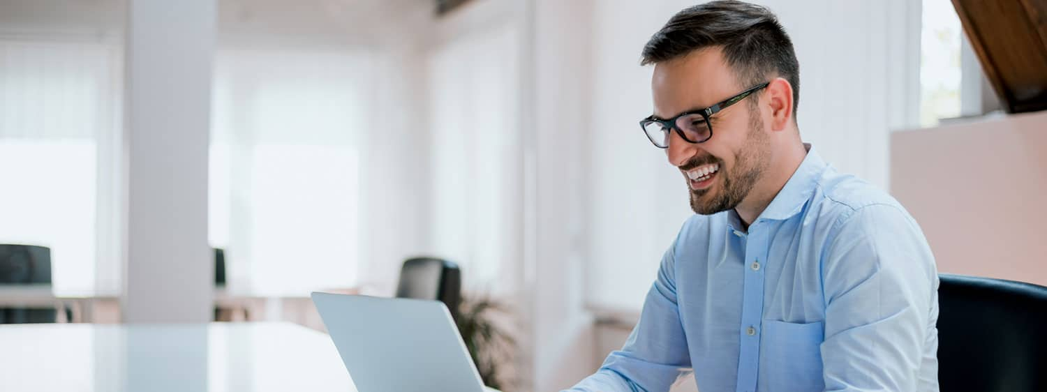 A person smiles while working on his laptop.
