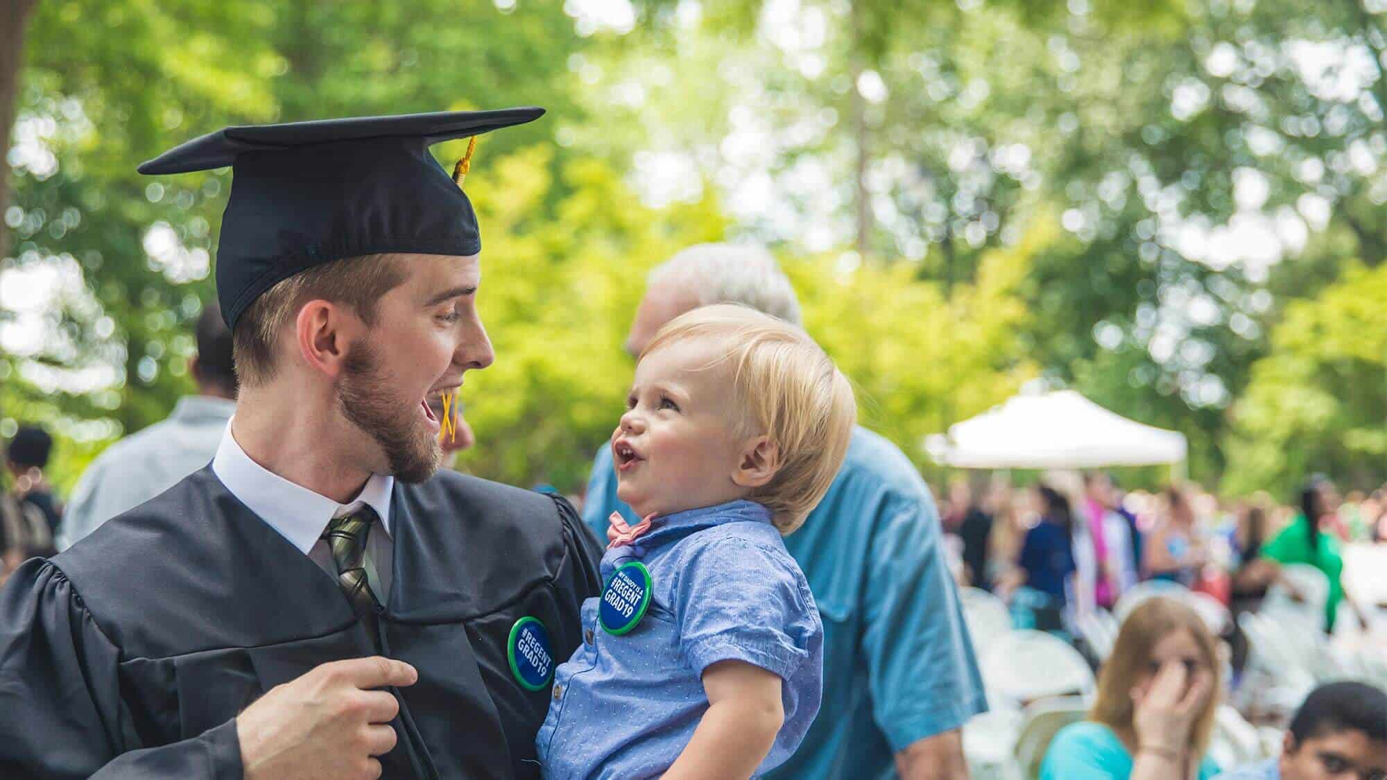 Earn your degree online at Regent University: An alumnus with his son on graduation day.