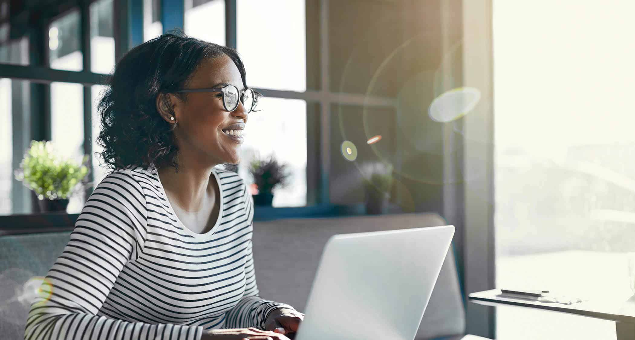 A lady working on her laptop: Explore Regent University's on-campus and online business and leadership degrees,
